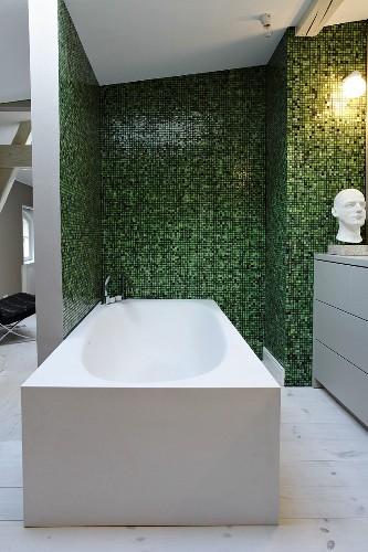 Modern free-standing bathtub in ensuite bathroom with green mosaic tiles