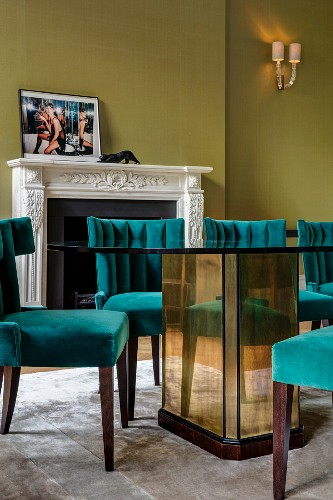Dining table with mirrored base and petrol-blue upholstered chairs in grand dining room