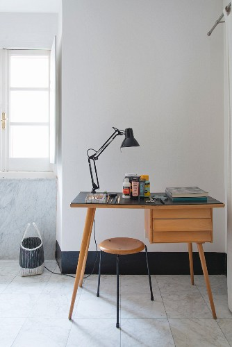 Desk lamp on desk and retro-style stool on marble-tiled floor