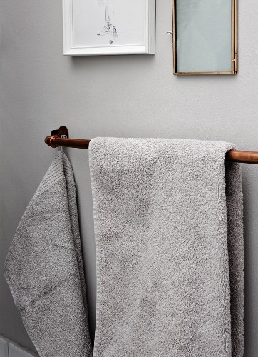 Copper piping used as towel rail mounted on wall