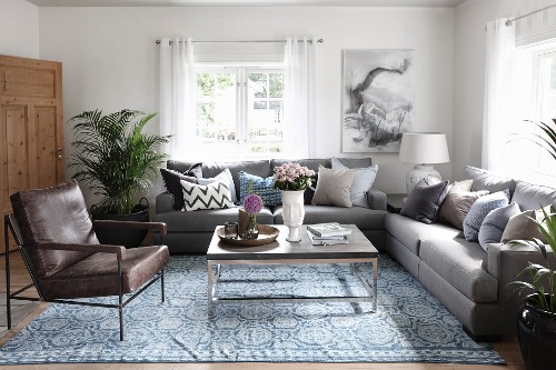Leather armchair and sofa set around modern coffee table and patterned rug in rustic living room