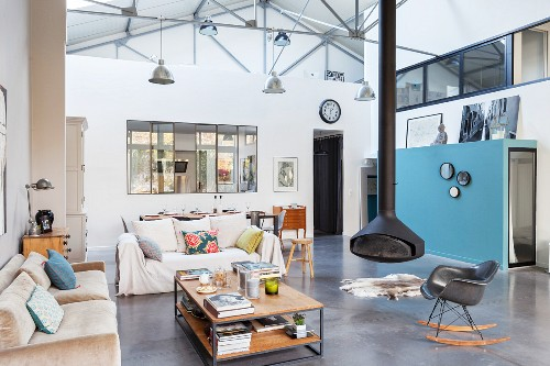 Suspended stove in open-plan living area of loft apartment