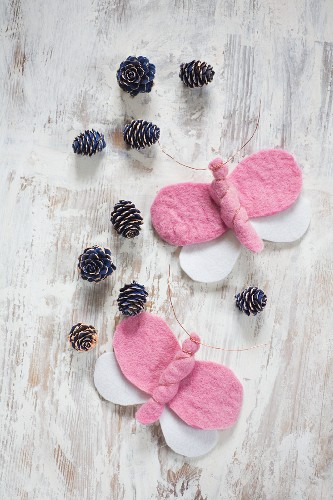 Pink and white, hand-made felt butterflies and blue-painted pine cones arranged on vintage wooden surface