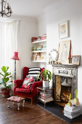 Red velvet wing-back chair next to artistic fire surround in cosy reading corner