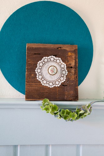 Ornament made from old piece of wood, doily and brooch