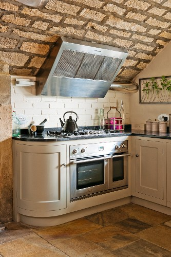 White country-house kitchen counter with rounded end cupboard and gas cooker under extractor hood on rustic, vaulted stone ceiling