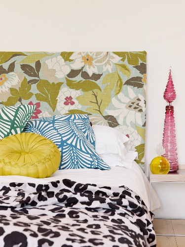 Detail of bed with floral headboard and scatter cushions