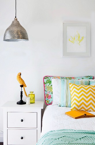 Bed with various pillows next to white bedside table with parrot figure