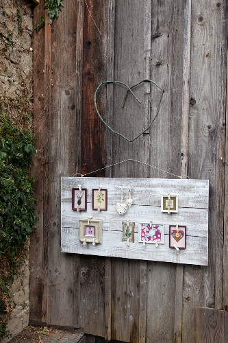 Gallery of pictures on old board and shutter dogs below love heart