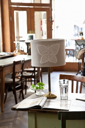 Lampshade decorated with crocheted butterfly motif in vintage-style cafe