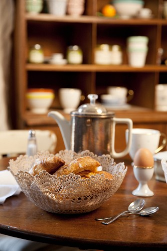 Bread basket made from lace doily on breakfast table