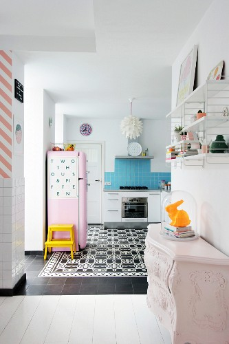 Rabbit ornament under glass cover on top of antique chest of drawers in front of open-plan kitchen with black and white cement floor tiles and pink fridge