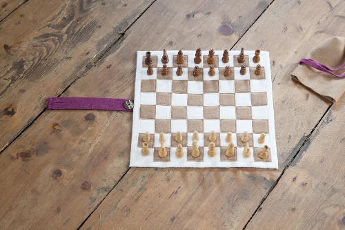 Hand-sewn boiled-wool chessboard and wooden chess pieces on rustic wooden floor