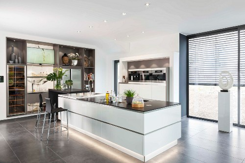 A white kitchen island with base lighting in an open-plan designer kitchen