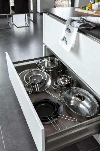 A kitchen island with an open drawer and a view of stainless steel pots