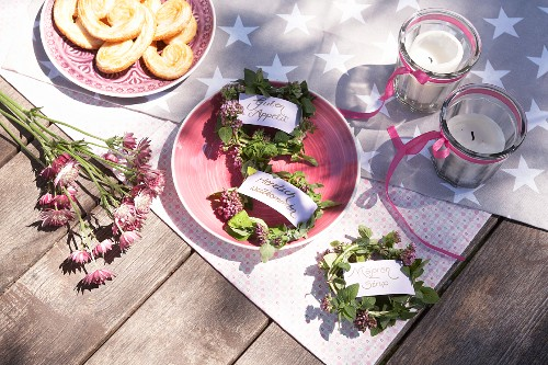 Tags on small wreaths of marjoram on picnic blanket