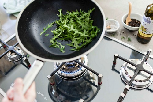 Rocket in a pan over a gas hob