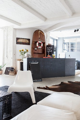 Lifebelt hung from wooden boat stood on end behind black kitchen counter in open-plan living area
