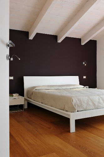 White bed against black wall in attic bedroom