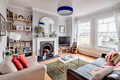 Open fireplace and huge windows in eclectic living room