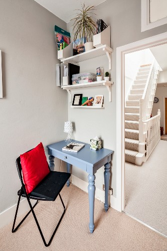 Desk with turned legs below wall-mounted shelves