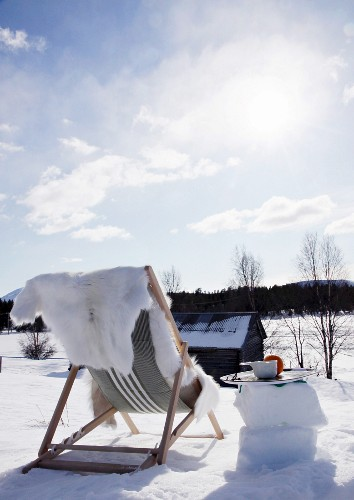 Fur blanket on lounger amongst snow under blue sky