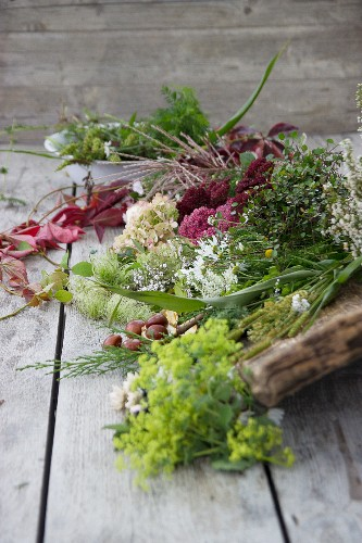 Autumnal arrangement of flowers and leaves on rustic wooden surface