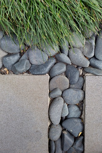 Slabs and pebbles next to ornamental grass