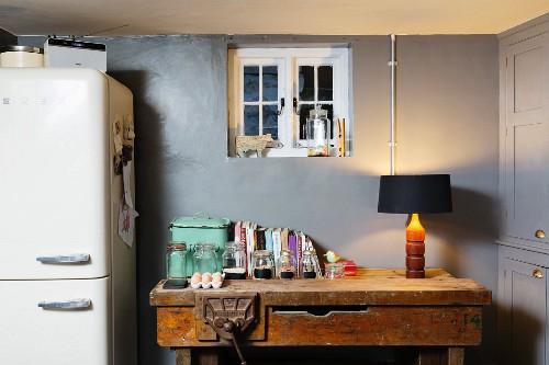 Old workbench in kitchen below small window in grey wall