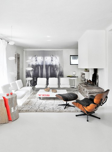 Designer furniture and chimney breast above rustic fireplace in elegant lounge