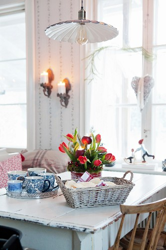 Advent arrangement of red tulips, bread basket and tray of cups on dining table