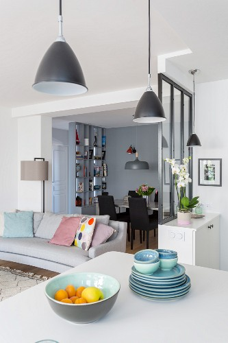 Crockery stacked on white worksurface, partition wall, couch and dining area in background
