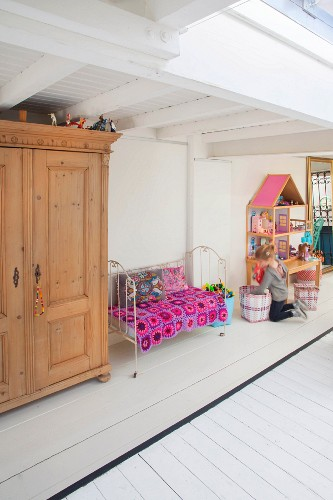 Little girl, dolls' house, vintage bed and wooden cupboard in play area