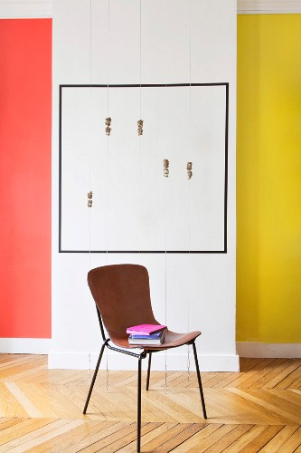 Books stacked on leather-covered chair in front of artwork and colourful walls