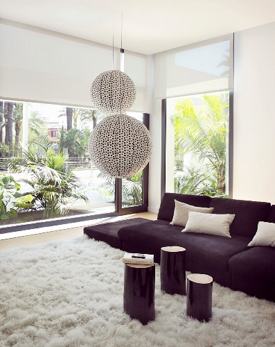 Black sofa and white rug in living room with glass wall