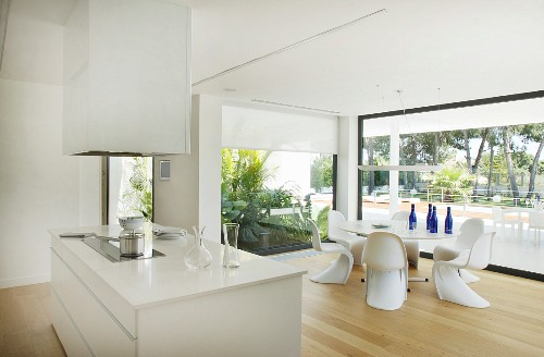 View across island counter to round dining table and panoramic windows