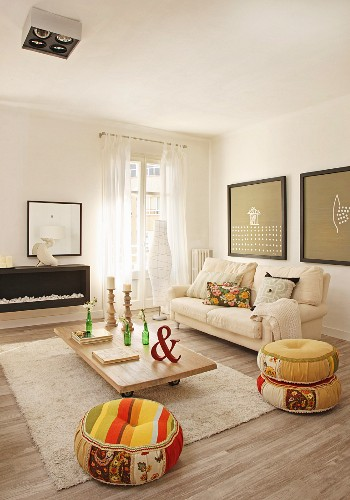 Cream flokati rug, low coffee table and colourful ethnic pouffes in comfortable living area