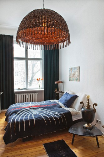 Double bed, vintage bedside lamp and pendant lamp with wicker lampshade in bedroom of period apartment