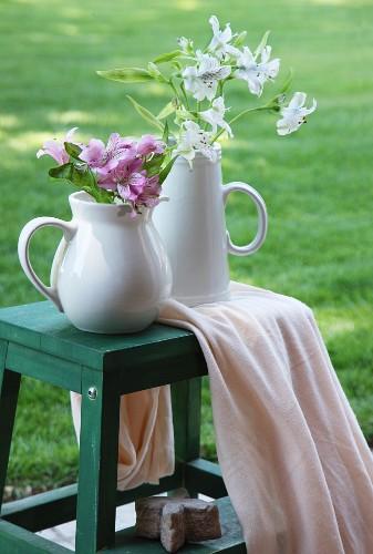 Flowers in jugs on green step stool in garden