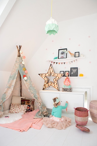 Little girl wearing tutu sitting next to play wigwam in vintage-style bedroom