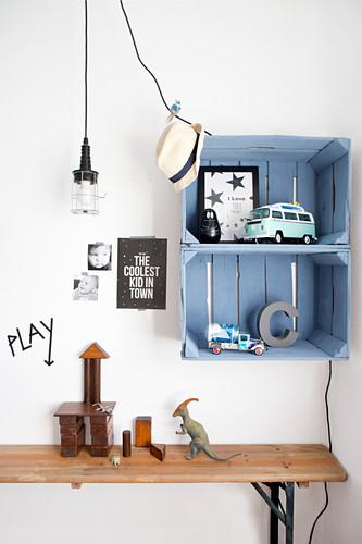 Blaue Holzkisten als Wandregal über einer Bierbank im Kinderzimmer