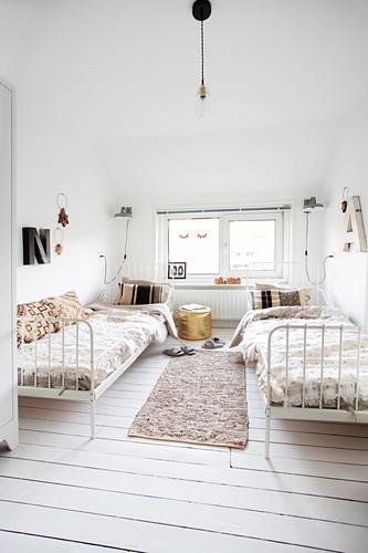 Schlafzimmer in Weiß mit zwei Metallbetten und Dielenboden