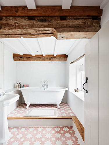 View of renovated bathroom with wooden beams and roll top bathtub