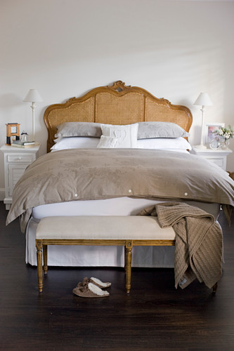 Bedroom bench at foot of antique bed in brown-and-white bedroom