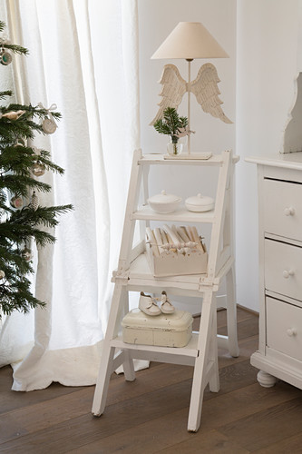 Vintage decorations and white table lamp on library step chair