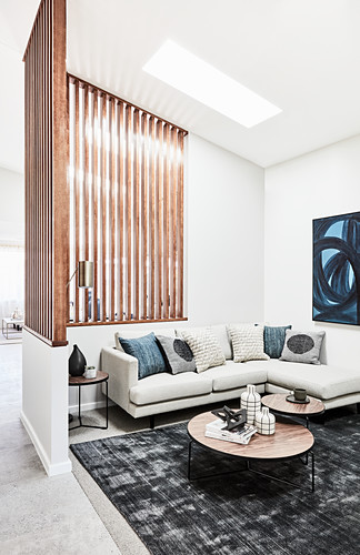 Pale corner sofa and set of coffee table in lounge area with slatted wooden partition