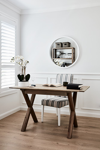Books and orchid on wooden table, chair with striped upholstery and round mirror on wall