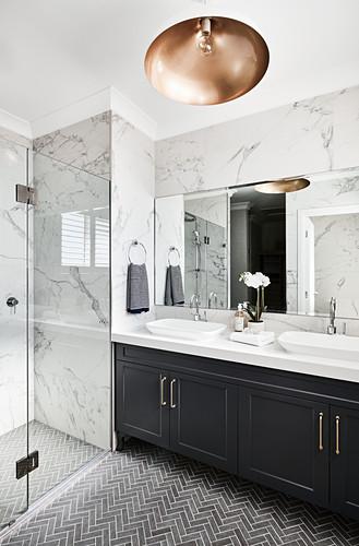 Wachtischmöbel in elegantem Badezimmer mit Marmorfliesen und Duschbereich