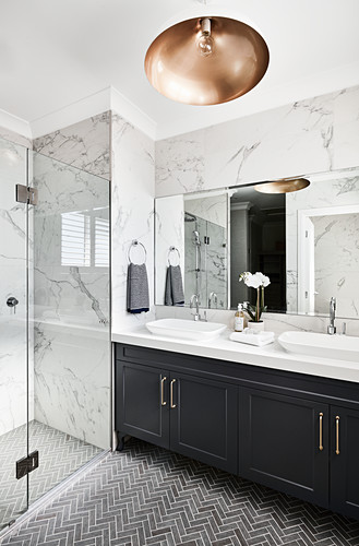 Washstand in elegant bathroom with marble tiles and shower area