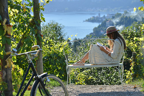Woman reading book sitting on bench with sea view